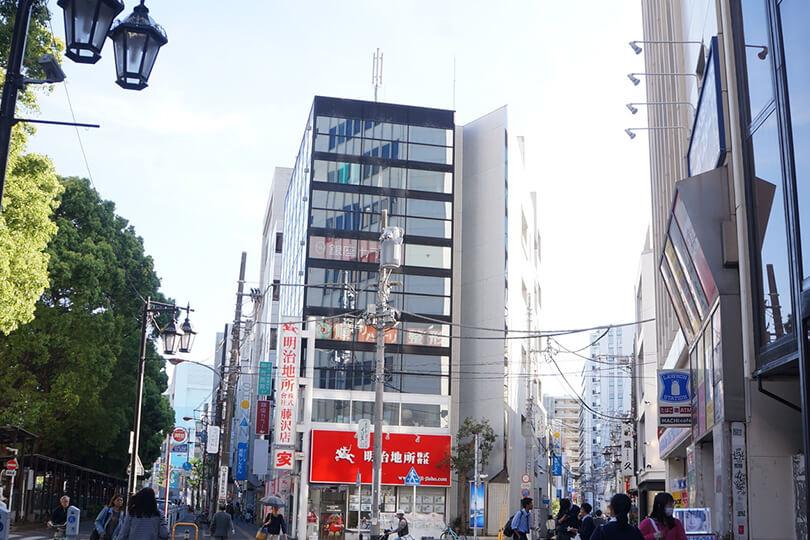オーパの前を通り抜けると、右手のローソンの先に、赤い看板「明治地所」の看板のあるビルの3階です